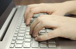 Closeupsikt av en hand med fingrar som skriver på en tangentbordsilverbärbar dator som ligger på ett trämattt Royaltyfri Foto