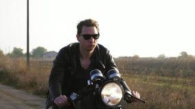 Closeupsikt av en stilfull kall ung man i solglasögon- och för läderomslag ridningmotorcykel på en asfaltväg på ett soligt stock video