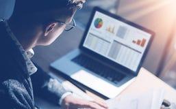 Closeupsikt av finansmarknadsanalytikeren i glasögon som arbetar på det soliga kontoret på bärbara datorn, medan sitta på trätabe Arkivfoto