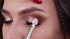 Closeupsikt av händer som applicerar ögonskuggor till ögonlock för ung kvinna i ultrarapid lager videofilmer