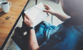 Closeupsikt av mannen som förestående rymmer den digitala minnestavlan och använder, medan sitta i fåtölj på det coworking ställe royaltyfri fotografi