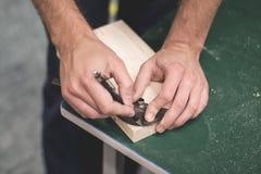 Closeupsikt av personhandinnehavet som mäter linjalhjälpmedlet 90 grader per stycke av trä för att klippa Arkivfoton