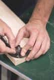 Closeupsikt av personhandinnehavet som mäter linjalhjälpmedlet 90 grader per stycke av trä för att klippa Fotografering för Bildbyråer