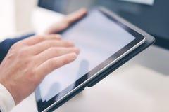 Closeupsikt av två manliga händer som rymmer den elektroniska minnestavlan och den rörande skärmen Affärsman som fungerar på kont Arkivfoto