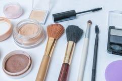 Closeupsikt på skönhetsmedel, makeup och borstar på vit bakgrund royaltyfria bilder