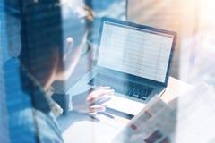 Closeupsikten av bankrörelsen finansierar analytikeren i glasögon som arbetar på det soliga kontoret på bärbara datorn, medan sit Royaltyfria Foton