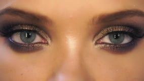 Closeupsikten av kvinna` s synar med härlig guld- makeupöppning och att stänga sig i slowmotion