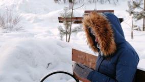 Closeupsikten av kvinnan sitter på bänk, och bläddra mobiltelefonen i vinterstad parkera under dagen i snöig väder stock video
