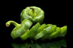 Closeupskivor av gröna spanska peppar på svart med droppar av wate Fotografering för Bildbyråer