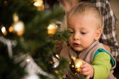 Closeupskott av en unge nära xmas-träd arkivbilder
