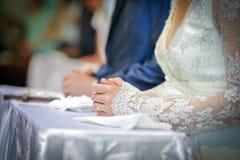 Closeupskott av händer av en brud. Brudens hand med förlovningsringen på och snör åt länge muffen Arkivbilder