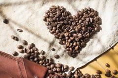 Closeupskott av hjärtaform som göras av kaffebönor på linnetorkduken Arkivbilder