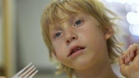 Closeupskott av lite pojken som äter en smaklig dillande i ett gatakafé Gatamatbegrepp stock video