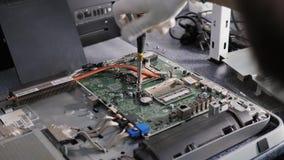 Closeupskott av manhänder som arbetar på demonterande och rengörande strömkretsbräde i bärbar dator genom att använda processorn  lager videofilmer