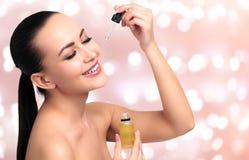 Closeupskott av olje- applicera för skönhetsmedel på framsida för ` s för ung kvinna Arkivfoto