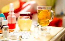 Closeupskott av te och mediciner på tabellen bredvid säng Royaltyfria Bilder