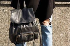 Closeupskottet av den svarta läderryggsäcken på kvinna`en s lägger benen på ryggen Royaltyfria Bilder