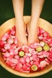 Closeupskottet av fot för en kvinna doppade i vatten med kronblad i en träbunke Royaltyfri Bild