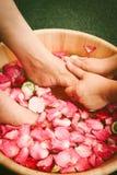 Closeupskottet av fot för en kvinna doppade i vatten med kronblad i en träbunke Fotografering för Bildbyråer