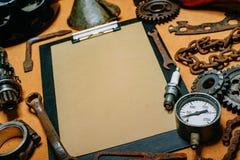 Closeupskrivplatta med pappers- For Your Information i mitten av hjälpmedel, kugghjul på tappningmetallbakgrund Motorcykelutrustn royaltyfri bild