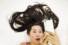 Closeupstående av asiatiska kvinnor som ligger på jordning med svart långt hår agera överraska, och plying av telefonen arkivbilder