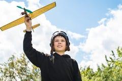 Closeupstående av att le pojken med den plana modellen på himmelbackgrou arkivbild