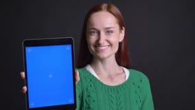 Closeupstående av attraktivt caucasian kvinnligt bläddra ner på minnestavlan och uppvisning av dess skärm till att le för kamera lager videofilmer