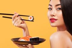 Closeupstående av den asiatiska kvinnan som äter sushi och rullar på en gul bakgrund Royaltyfri Fotografi