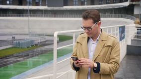 Closeupstående av den attraktiva caucasian mannen som kontrollerar telefonen och får lycklig och förvånad stående det fria i stock video