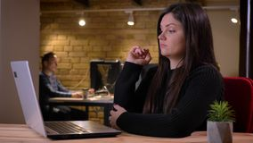 Closeupstående av den bekymrade vuxna caucasian affärskvinnan som får frustrerad och förvirrad, medan arbeta på bärbara datorn arkivfilmer
