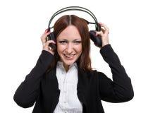 Closeupstående av den gulliga unga affärskvinnan med hörlurar som isoleras på vit fotografering för bildbyråer