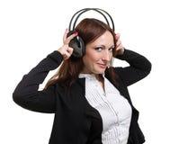 Closeupstående av den gulliga unga affärskvinnan med hörlurar som isoleras på vit royaltyfria bilder