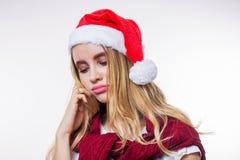 Closeupstående av den härliga blonda kvinnan för ledsen rubbning som bär den röda jultomtenhatten på vit bakgrund Dåligt lynne, b arkivbild