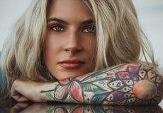 Closeupstående av Den härliga flickan satte hennes huvud i hennes armar med tatueringar förväntan Arkivfoto