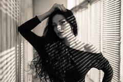 Closeupstående av den härliga sexiga brunettflickan som har gyckel som ser sensually kameran på sol tänd rullgardinbakgrundssvart Arkivfoto