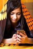 Closeupstående av den härliga tonårs- flickan som använder den dolde mobil telefonen royaltyfri fotografi