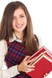 Closeupstående av den lyckliga studenten som rymmer en hög av böcker royaltyfria foton
