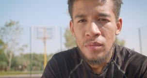 Closeupstående av den manliga basketspelaren för ung stilig afrikansk amerikan som bestämms se att sitta för kamera stock video
