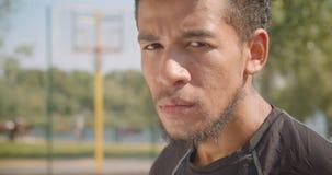 Closeupstående av den manliga basketspelaren för ung stilig afrikansk amerikan som ser kameran som den är trött sitta stock video