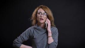 Closeupstående av den medelåldersa överdådiga rödhårig mankvinnlign i exponeringsglas som har en tillfällig konversation på telef royaltyfri foto
