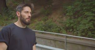 Closeupstående av den motiverade sportiga manliga joggeren för vuxen människa som utomhus går ner trappan på gatan i den stads- s stock video
