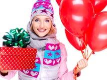 Closeupstående av den roliga lyckliga vuxna kvinnan med den röda gåvaasken och Arkivfoton