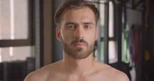 Closeupstående av den shirtless muskulösa caucasian mannen som ser kameran med beslutsamhet som inomhus står i idrottshallen arkivfilmer