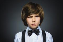 Closeupstående av den stiliga pojken med förvånat uttryck, medan stå mot grå bakgrund royaltyfri foto