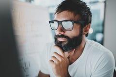 Closeupstående av den stiliga skäggiga mannen som arbetar på den moderna kontorsvinden horisontal suddighet bakgrund kantjusterat fotografering för bildbyråer