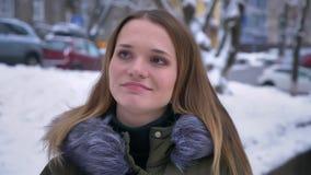 Closeupstående av den unga attraktiva brunettcaucasainkvinnlign som ler och ser kameran i begrundande i ett pråligt arkivfilmer