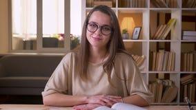 Closeupst?ende av den unga attraktiva caucasian kvinnliga studenten i exponeringsglas som ser kameran som lyckligt inomhus ler in