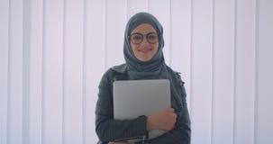 Closeupstående av den unga attraktiva muslim affärskvinnan i hijab och exponeringsglas som ser kameran som rymmer en bärbar dator stock video