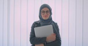 Closeupstående av den unga attraktiva muslim affärskvinnan i hijab och exponeringsglas som ser kameran som rymmer en bärbar dator lager videofilmer