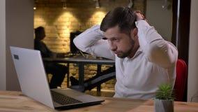Closeupstående av den unga caucasian affärsmannen som arbetar på bärbara datorn som får frustrerad och trött i kontoret